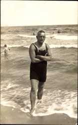 Foto Ak Mann in dunklem Badeanzug am Strand, Kurzes Haar