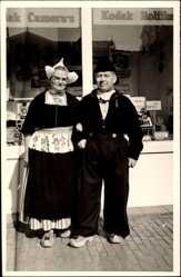 Foto Ak Älteres Paar in Trachten vor einem Geschäft, Kodak Fotoapparate