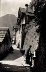 Postcard Hallstatt Oberösterreich, Häusergasse, Brunnen, Frau mit Eimer