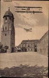 Postcard Fischamend Niederösterreich, Biplan, Flugzeuge, Turmuhr, Platz