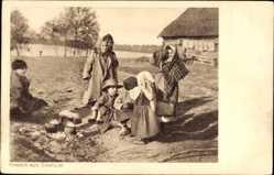 Ak Sadolsk Polen, Kinder aus dem Ort, Töpfe, Kopftücher, Gebäude